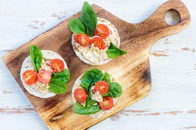 Gesunder snack aus reiskuchen mit hummus, spinat und tomaten