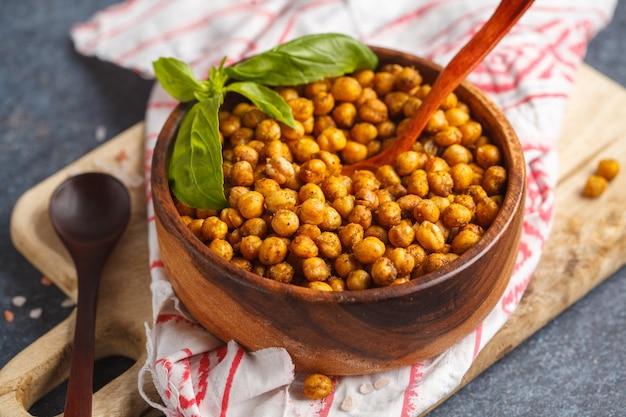 Gesunder snack - gebackene würzige kichererbsen in einer holzschale. gesundes veganes lebensmittelkonzept.