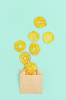 Gesunder snack. hausgemachte dehydrierte fruchtchips der mandarine. trockene mandarine in papierverpackung.