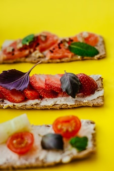 Gesunder snack mit knäckebrot, frischkäse, erdbeere, pampelmuse, tomate und gurke auf einem gelben hintergrund