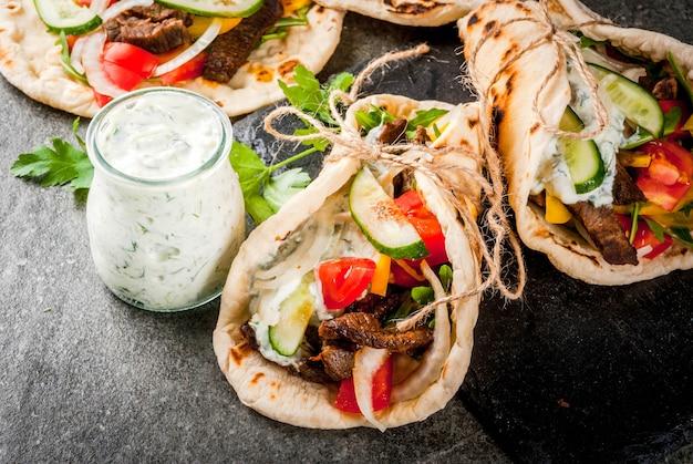 Gesunder snack, mittagessen. traditionelle griechische sandwichgyros - tortillas, fladenbrot mit einer füllung aus gemüse, rindfleisch und sauce tzatziki