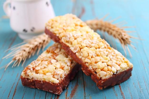 Gesunder snack, müsliriegel mit rosinen und nüsse auf blauem grund