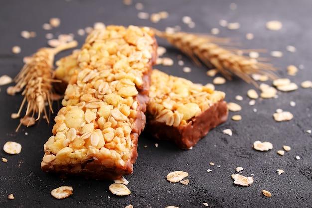Gesunder snack, müsliriegel mit rosinen und nüsse auf einem schwarzen hintergrund