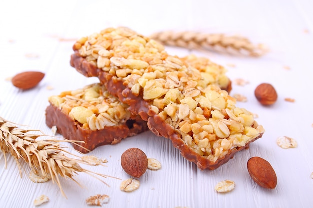 Gesunder snack, müsliriegel mit rosinen und nüsse auf einem weißen hintergrund
