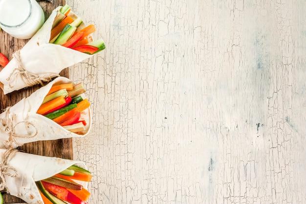 Gesunder snackaperitif des sommers, tortillasandwichverpackungen der mexikanischen art sortierten bunte frischgemüsestöcke (sellerie, rhabarber, pfeffer, gurke und karotte) mit jogurtsoßenbad oben