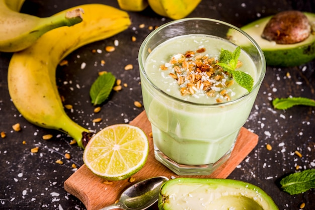 Gesunder sommergetränkavocado und banane smoothie mit dunklem rostigem hintergrund des kalkgranolas und der kokosmilch