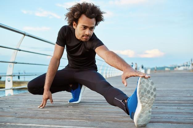 Gesunder sportler dunkelhäutiger junge, der sich am morgen auf holzplattform ausdehnt. sportlicher mann mit buschiger frisur, die seine beine aufwärmt