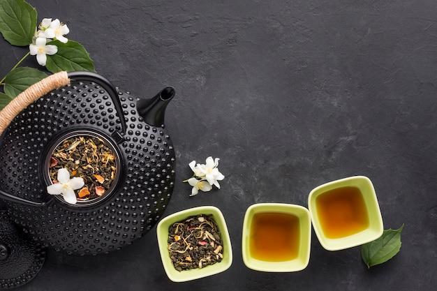 Gesunder tee mit aromatischem trockenem tee in den schüsseln und in der teekanne auf schwarzer oberfläche