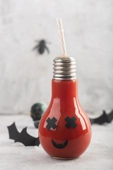 Gesunder tomatensaft halloweens im glasgefäß mit furchtsamem gesicht auf grau