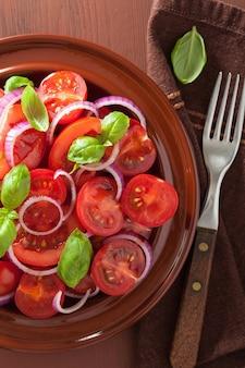 Gesunder tomatensalat mit zwiebel-basilikum-olivenöl und balsamico-essig