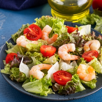 Gesunder und diät-salat mit garnelen, tomaten und gemischtem grün.