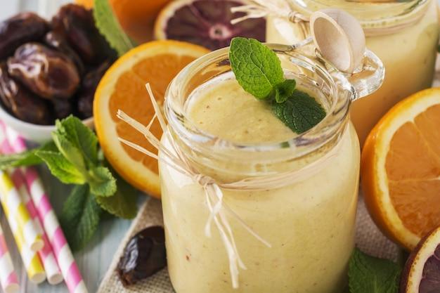 Gesunder und frischer orangen- und dattelfrucht-smoothie auf blauem holztisch. selektiver fokus.