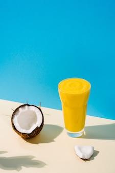 Gesunder und köstlicher veganer mango- und kokosnuss-smoothie kopierraum beiger und blauer hintergrund