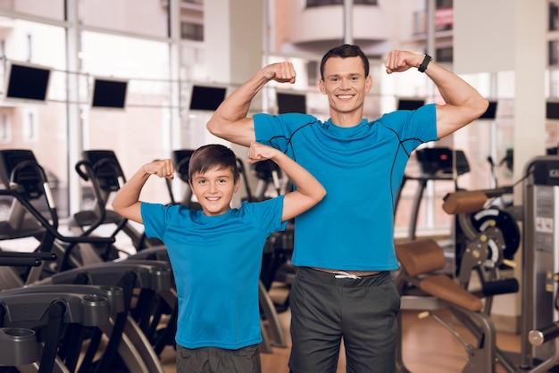 Gesunder vater und sohn zeigen muskulatur.