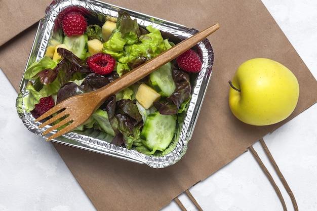 Gesunder veganer salat zum mitnehmen in aluminiumbehältern oder zur lieferung von lebensmitteln.