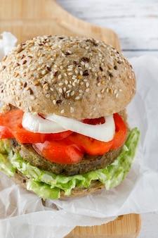 Gesunder veganer tofu-burger mit spinat, salat, tomate, zwiebel und gebratenem gemüse
