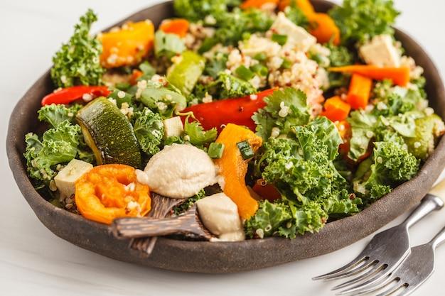 Gesunder vegansalat mit gebratenem gemüse, tahini, quinoa und kohl. sauberes essen konzept.