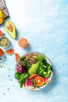 Gesunder vegetarischer buddha-schüsselsalat mit obst, gemüse und samen auf einem blauen hintergrund. vertikales bild, platz für text.