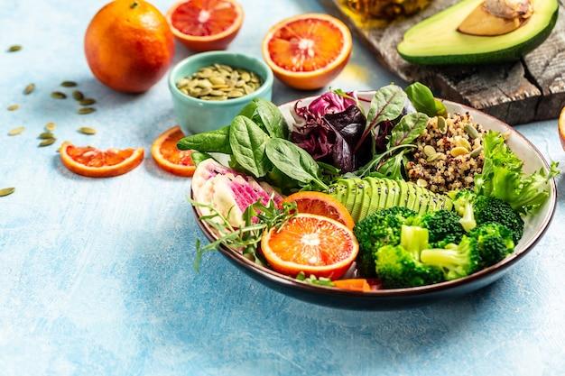 Gesunder vegetarischer buddha-schüsselsalat mit obst und gemüse auf blauem grund.