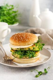 Gesunder vegetarischer burger mit ei- und erbsensprossen und samen mikrogrün, frischer salat, gurkenscheibe auf einem holzbrett auf hellem hintergrund. selektiver fokus