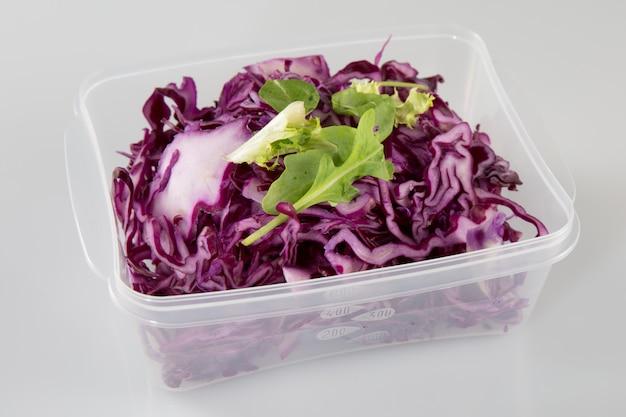 Gesunder vegetarischer salat mit dem rotkohl, der im plastik gehackt wird, nehmen kasten weg