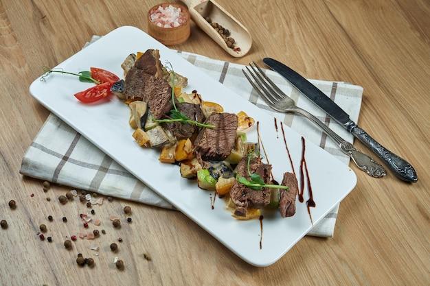 Gesunder warmer salat mit gegrilltem rindfleisch und gemüse auf einem weißen keramikteller. zusammensetzung mit salat und gewürzen auf einem holztisch. lebensmittelfotografie