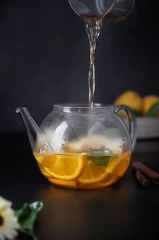 Gesunder warmer schwarzer tee mit früchten und minze in glasteekanne, über schwarzem hintergrund