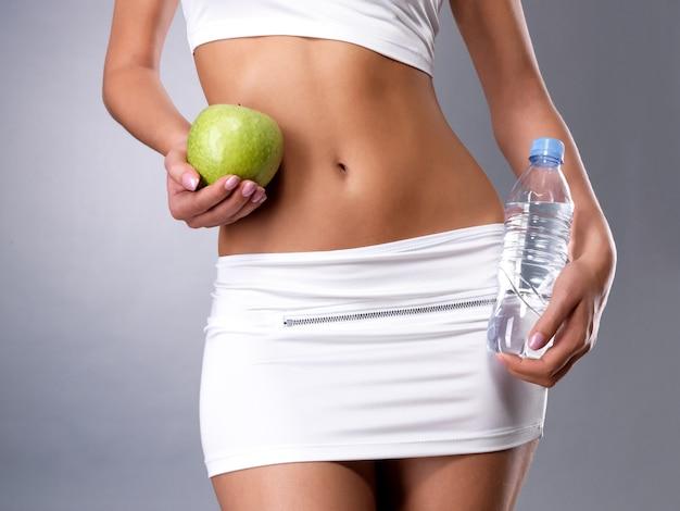 Gesunder weiblicher körper mit apfel und flasche wasser. gesundes fitness- und ess-lebensstil-konzept.