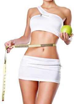 Gesunder weiblicher körper mit apfel und maßband. gesundes fitness- und ess-lebensstil-konzept.