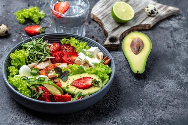 Gesundes abendessen. buddha bowl-mittagessen mit gegrilltem hühnchen und avocado, feta-käse, wachteleiern, erdbeeren, nüssen und salat. trend zum gesunden essen. ansicht von oben.