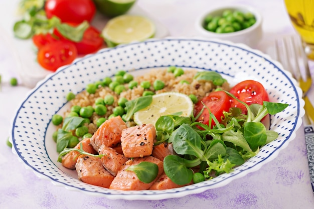 Gesundes abendessen. gegrillte lachsscheiben, quinoa, grüne erbsen, tomaten, limetten und salatblätter