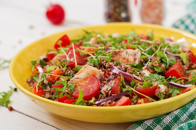 Gesundes abendessen. salatschüssel mittagessen mit gegrilltem hähnchen und quinoa, tomaten, paprika, roten zwiebeln und rucola