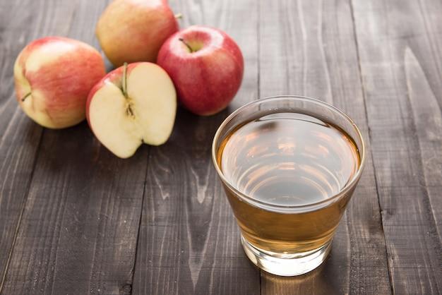 Gesundes apfelsaftgetränk und rote apfelfrüchte auf holztisch