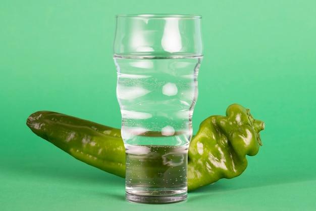 Gesundes arrangement mit wasser und grünem pfeffer