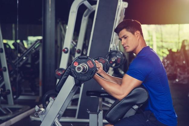 Gesundes asiatisches manntraining im turnhallentrainingssport mit dummkopf mit sportkleidung