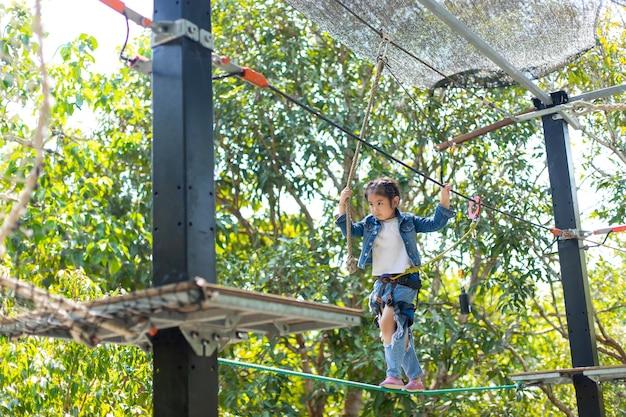 Gesundes asiatisches teenagermädchen, das aktivität in einem kletterabenteuerpark im sommerlager genießt.