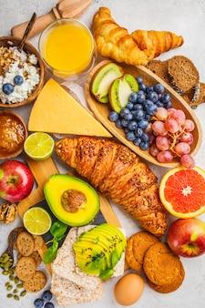 Gesundes ausgeglichenes frühstück auf weißem hintergrund. müsli, saft, croissants, käse, kekse und obst, draufsicht.