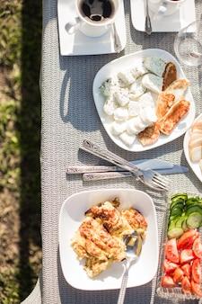 Gesundes ausgewogenes frühstück mit käse, keksen und frischem obst auf dem frühstückstisch in einem bauernhaus