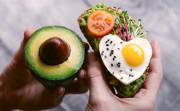 Gesundes bruschetta-frühstück mit avocado microgrin und rühreiern aus wachteleiern