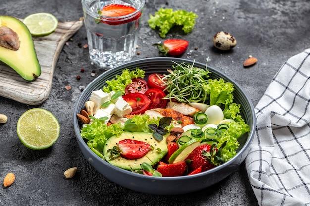 Gesundes buddha-bowl-mittagessen mit gegrilltem hühnchen und avocado, feta-käse, wachteleiern, erdbeeren, nüssen und salat. köstliches ausgewogenes lebensmittelkonzept.