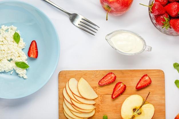 Gesundes dessert mit hüttenkäse und erdbeeren in der blauen platte auf einer weißen tischdecke