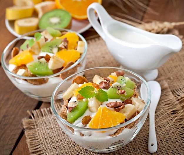 Gesundes dessert mit müsli und obst in einer glasschüssel auf dem tisch