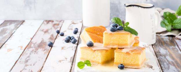 Gesundes dessert. selbst gemachter puddingkuchen mit vanillepuddingcreme und -blaubeeren.