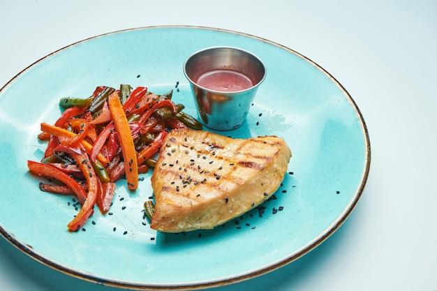 Gesundes, diätetisches essen - gegrilltes putenfilet mit gekochten karotten und brokkoli in einer blauen keramikplatte isolierte hellgraue oberfläche.