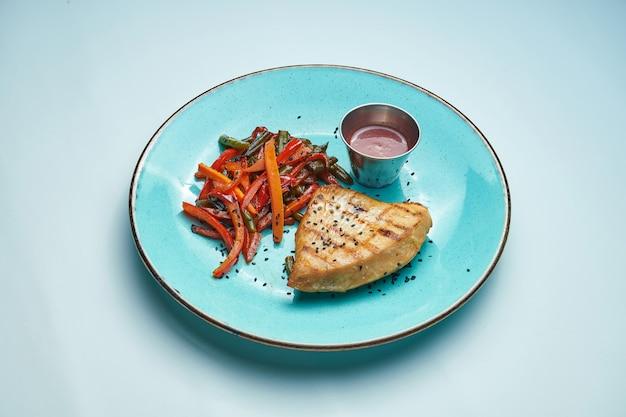 Gesundes, diätetisches essen - gegrilltes putenfilet mit gekochter karotte und paprika in einer blauen keramikplatte isolierte hellgraue oberfläche