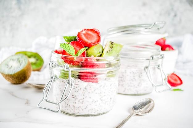 Gesundes diätetisches frühstück des strengen vegetariers, jogurt mit chia samen und frische früchte, erdbeeren, kiwi weißer marmorhintergrund-kopienraum