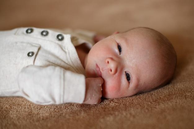 Gesundes einmonatiges neugeborenes auf beiger wand. muschelhaut im neugeborenen gesicht. porträt eines schönen frühgeborenen. baby, das auf einem weichen braunen laken auf bett im schlafzimmer nah oben liegt.