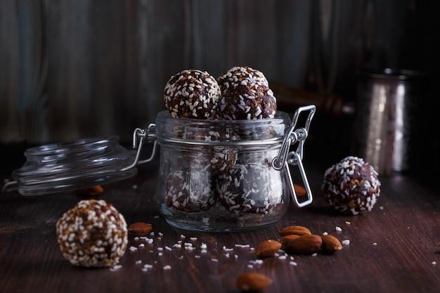 Gesundes energie-müsli mit nüssen, datteln, honig und sesam im glas