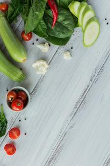 Gesundes essen auf weißem holztischmodell. leckeres, biologisches, leckeres und reifes gemüse