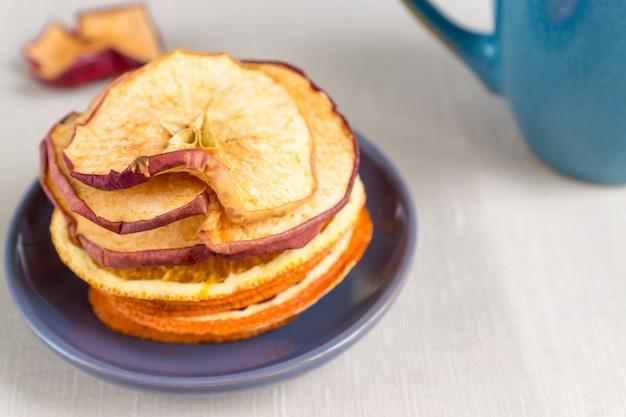 Gesundes essen bio-ernährung. geschnittener und getrockneter apfel, orange auf textilhintergrund.